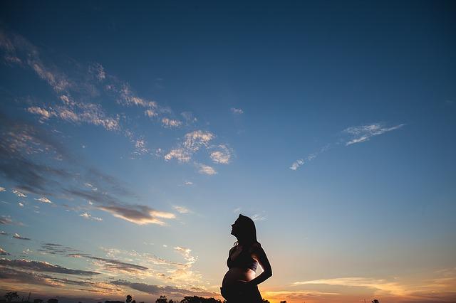 Kobieta w ciąży patrzy na zachód słońca