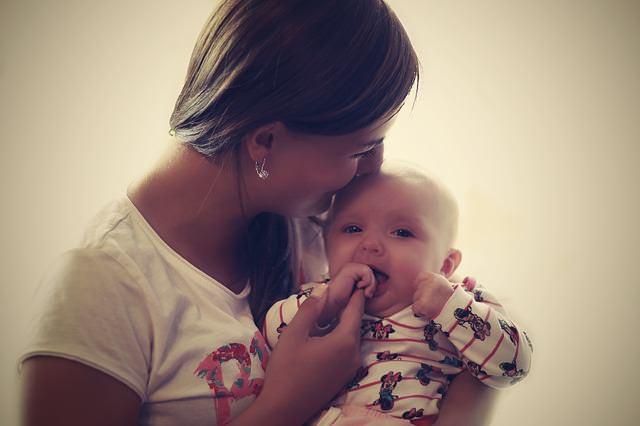 Matka całuje dziecko w główkę