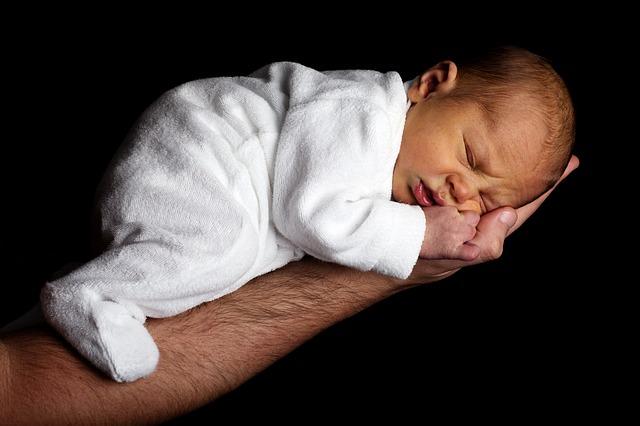 Niemowlę śpi na wyciągniętej dłoni
