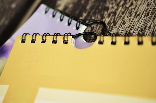 Notesy i zeszyty rozrzucone na stole