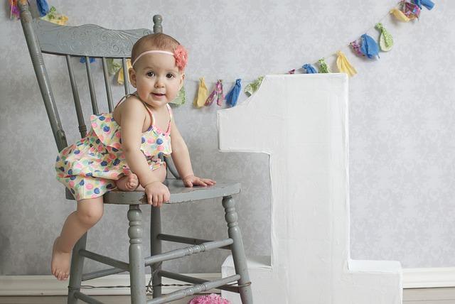 Dziecko w kolorowej sukience na krześle, obok wiszą kolorowe ozdoby