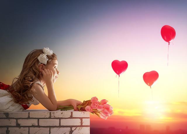 Dziewczynka na murku, w powietrzu baloniki z serduszkami