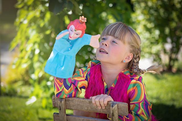 Kolorowo ubrana dziewczynka pokazuje pacynkę