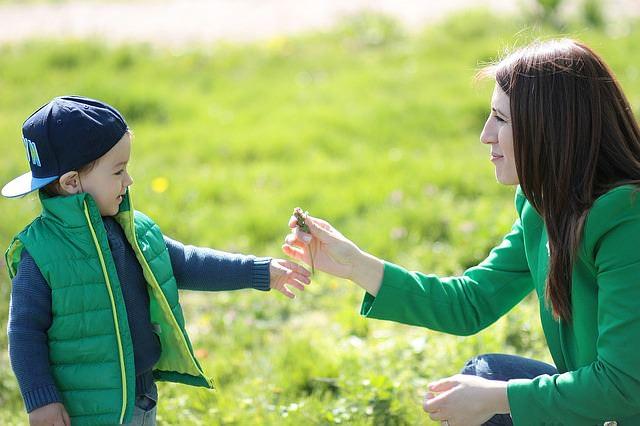 Mama z dzieckiem na spacerze pokazuje kwiatka