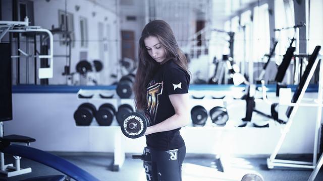 kobieta ćwiczy z hantami na siłownię