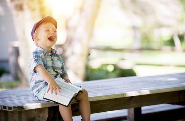 Śmiejący się chłopiec z książką