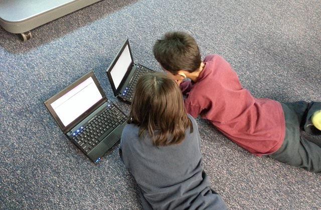 Dzieci leżące na podłodze z komputerami