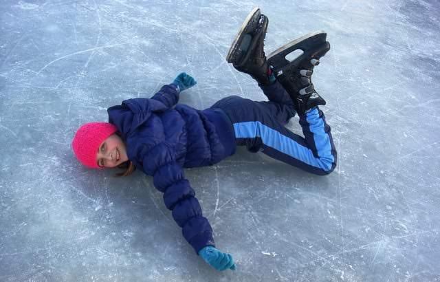 Dziecko leżace na lodzie w łyżwach