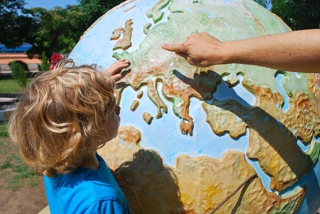 Rodzic pokazuje dziecku kontynent na globusie