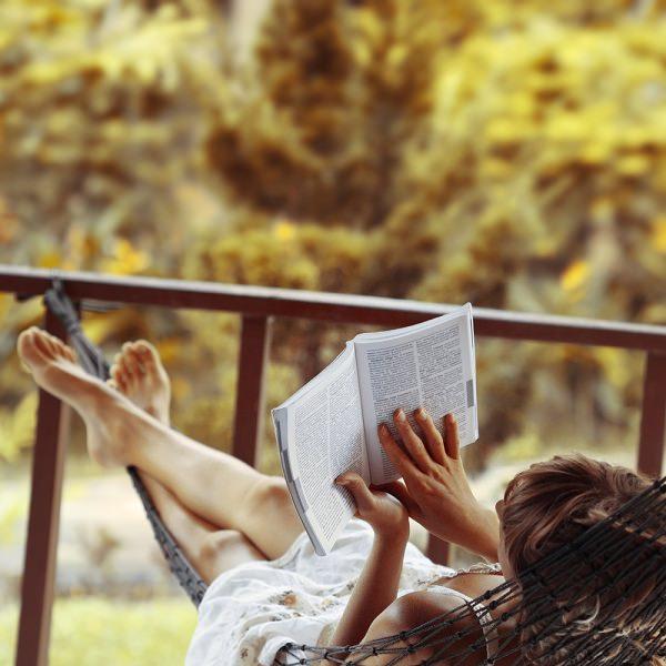 Kobieta czyta książkę na hamaku