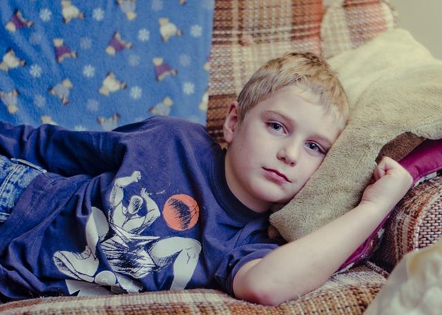 Chory chłopiec leży na kanapie