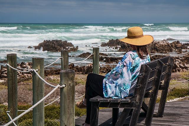 Kobieta w kapeluszu siedzi na krześle nad morzem