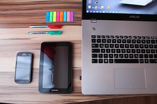 Laptop, telefon komórkowy, kolorowe karteczki i długopisy