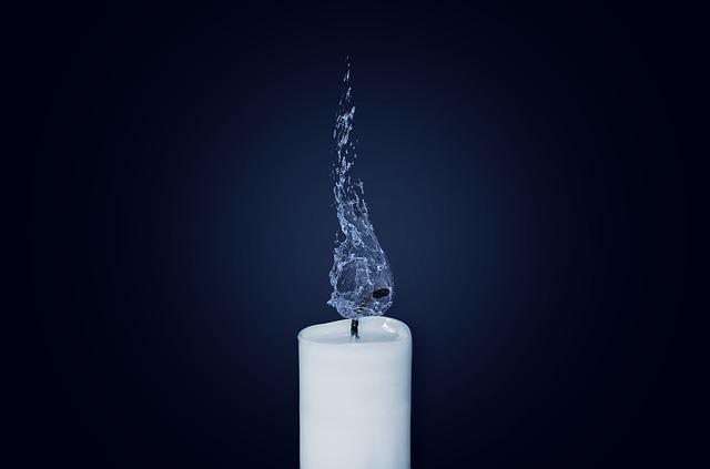 Biała świeca z knotem zalanym wodą