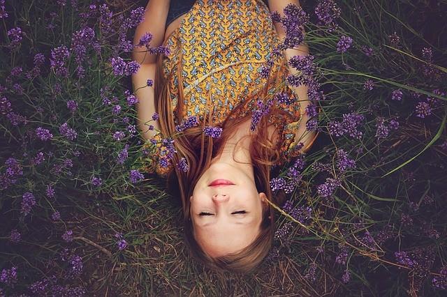 Kobieta leży na łące pełnej lawendy