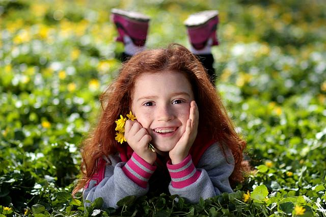 Dziewczynka leży na łące i uśmiecha się