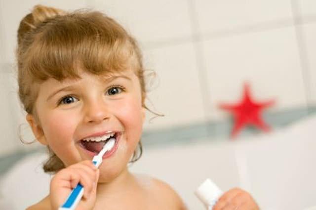 Blondwłosa dziewczynka myje ząbki