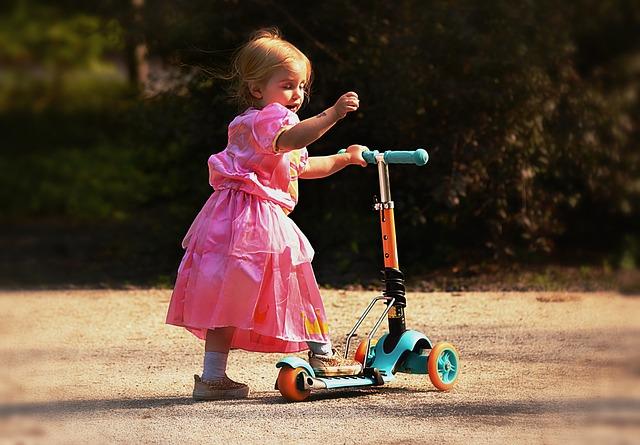 Dziewczynka w sukience na hulajnodze