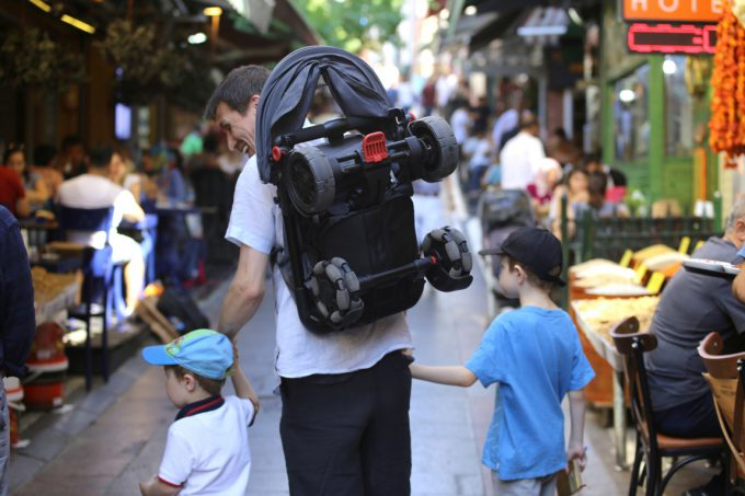 Ojciec z dziećmi i wózkiem na plecach