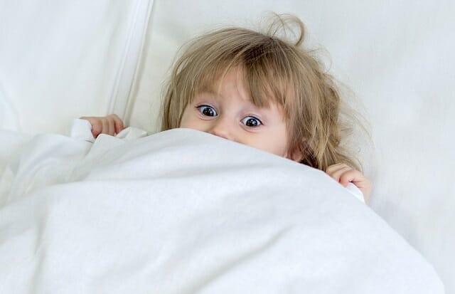 Dziecko leżące pod kołdrą